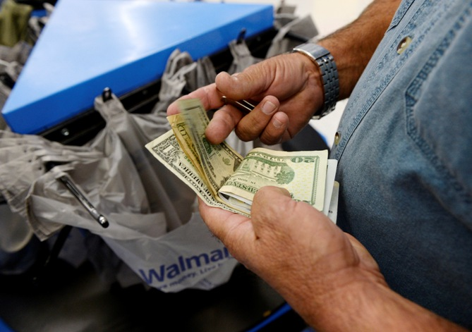 A customer counts his cash at the checkout lane of a Walmart store in the Porter Ranch section of Los Angeles.