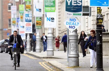 A man cycles past posters in central Dublin ahead of a fiscal treaty referendum in Ireland.