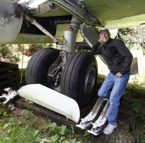 Bruce Campbell leans on a tyre of his Boeing 727 home.