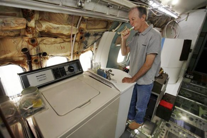 Bruce Campbell brushes his teeth at a sink in his Boeing 727 home in the woods outside the suburbs of Portland.