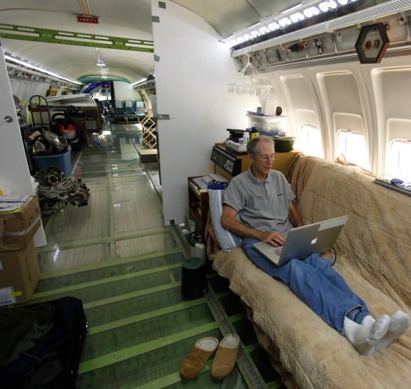 Bruce Campbell sits on his futon bed while using a laptop in his Boeing 727 home in the woods outside the suburbs of Portland.