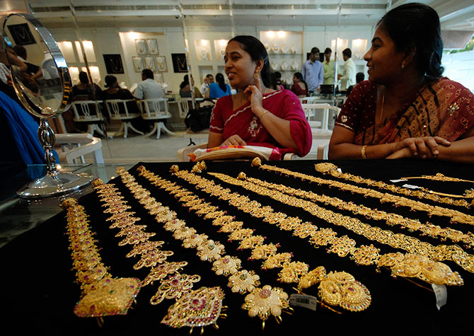 A customer looks in a mirror after wearing a gold earring inside a jewellery shop in Hyderabad.
