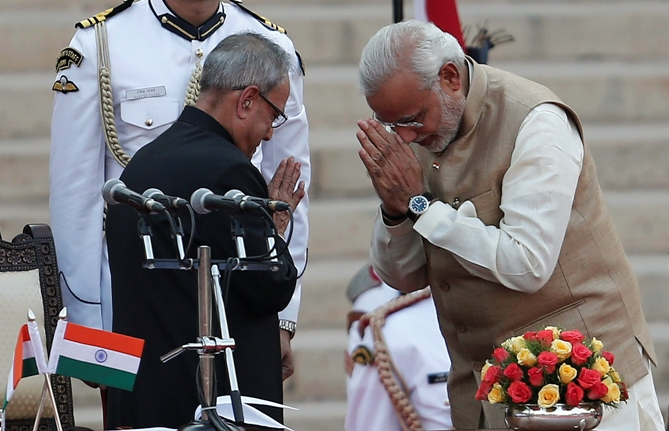 Prime Minister Narendra Modi (R) greets President Pranab Mukherjee after taking his oath at the presidential palace in New Delhi May 26, 2014.