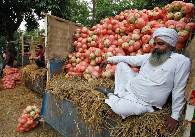 A farmer sits on a trolley loaded with melons as he waits for customers at a fruit and vegetable market in Chandigarh.