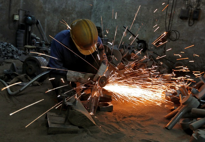 A worker grinds a metal shaft metal used in water pumps at a manufacturing unit on the outskirts of Ahmedabad.
