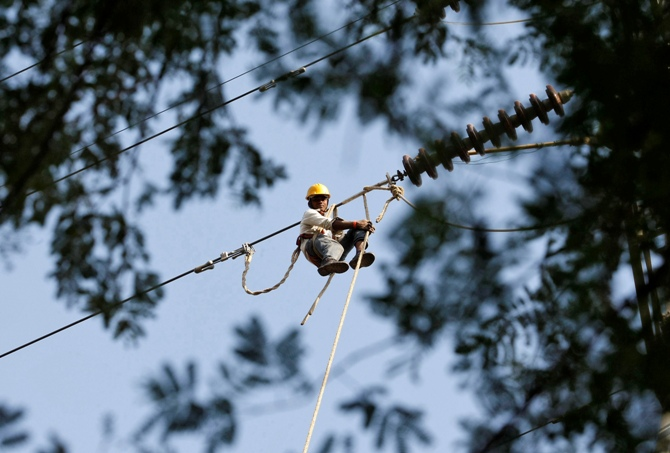 An employee for the Paschim Gujarat Vij Company Ltd. sets up power lines at Gandhinagar.