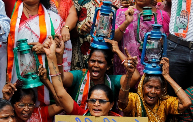 Demonstrators holding kerosene lanterns shout slogans during a protest against a power tariff hike, in Ahmedabad.