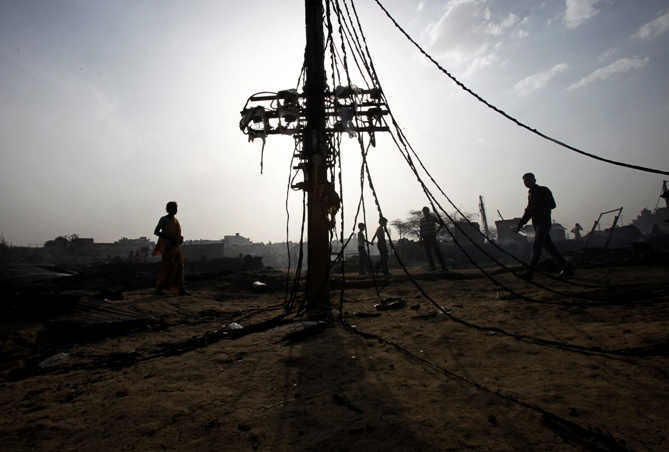 Local residents walk past burnt electrical cables after a fire broke out in a slum area in New Delhi.