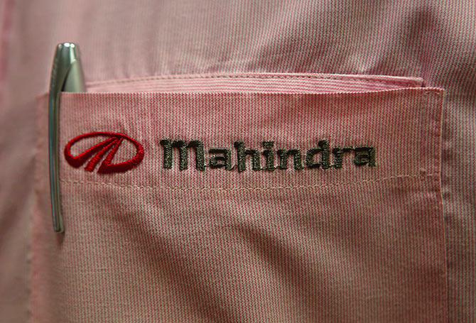The logo of Mahindra & Mahindra Ltd is pictured on the pocket of a salesman's shirt as he poses inside the company's showroom.
