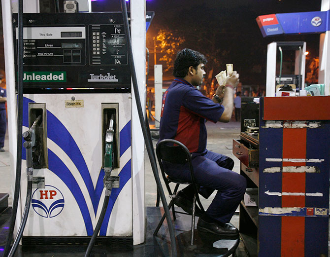 A worker (R) counts currency at a petrol pump in Kolkata.