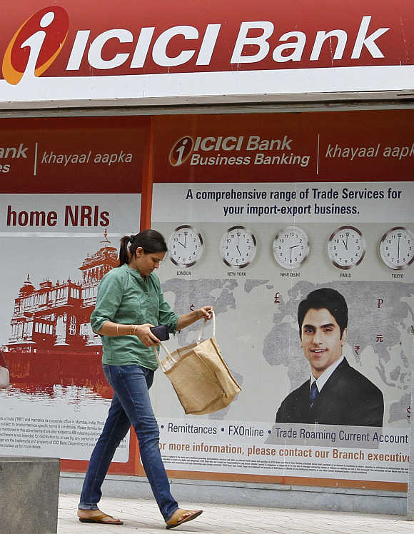 A woman walks past a ICICI Bank in the western Indian city of Ahmedabad.