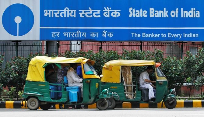 Auto rickshaws wait in front of the head office of State Bank of India (SBI) in New Delhi.