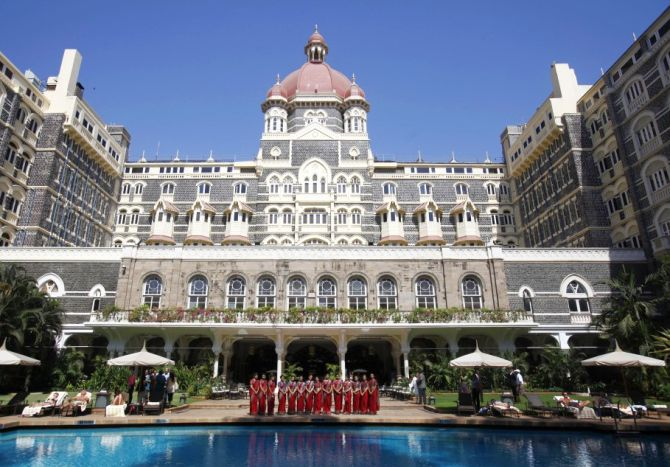 Staff of the Taj Mahal Palace hotel pose for a photo near the hotel's swimming pool.