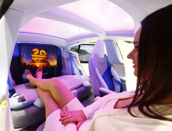 A model poses inside a concept car.