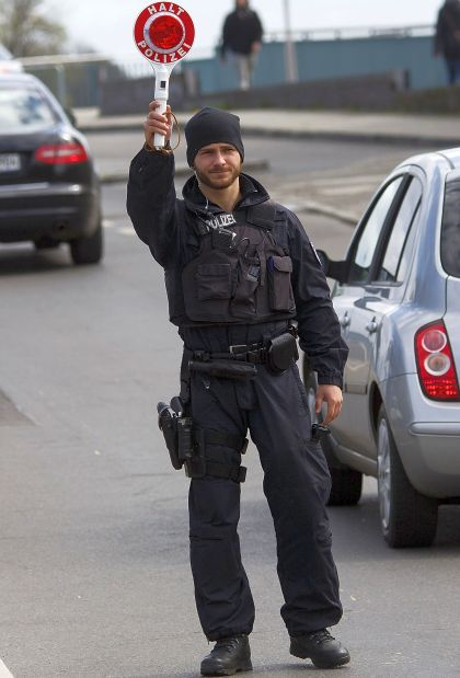 A German policman holds a police signal stick to stop cars.