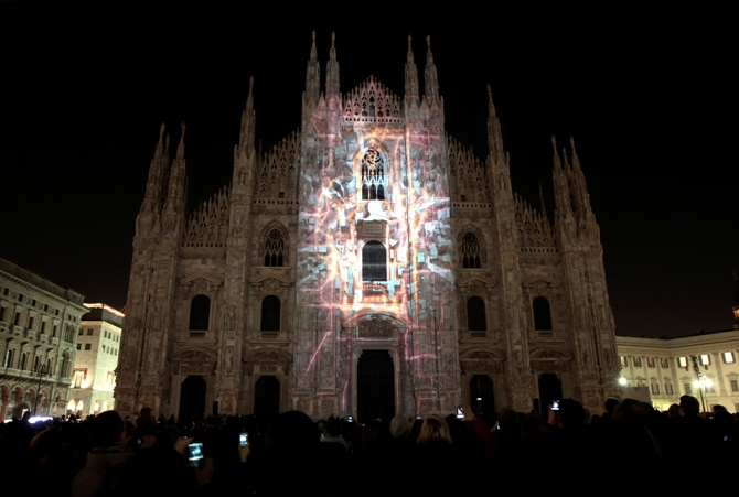 People take pictures during a video exhibition on the Duomo cathedral facade downtown in Milan, Italy