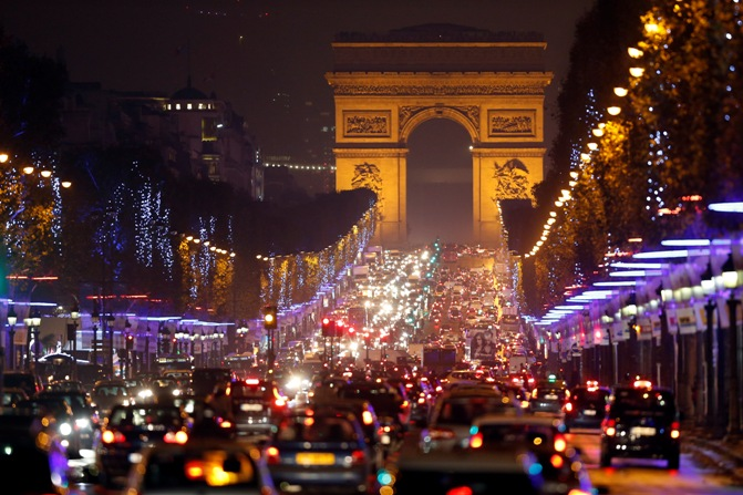 Christmas holiday lights decorate trees along the Champs Elysees with its Arc de Triomphe, in Paris.