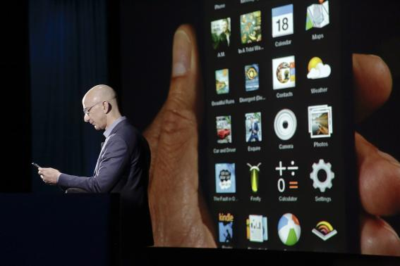 Amazon CEO Jeff Bezos shows off the 3D features of his company's new Fire smartphone at a news conference in Seattle, Washington
