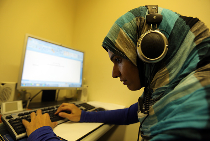 Sherien Fathy, a blind 32-year-old mother of two, uses her special headphones as she works on her computer at the General Petroleum Corporation in Cairo.