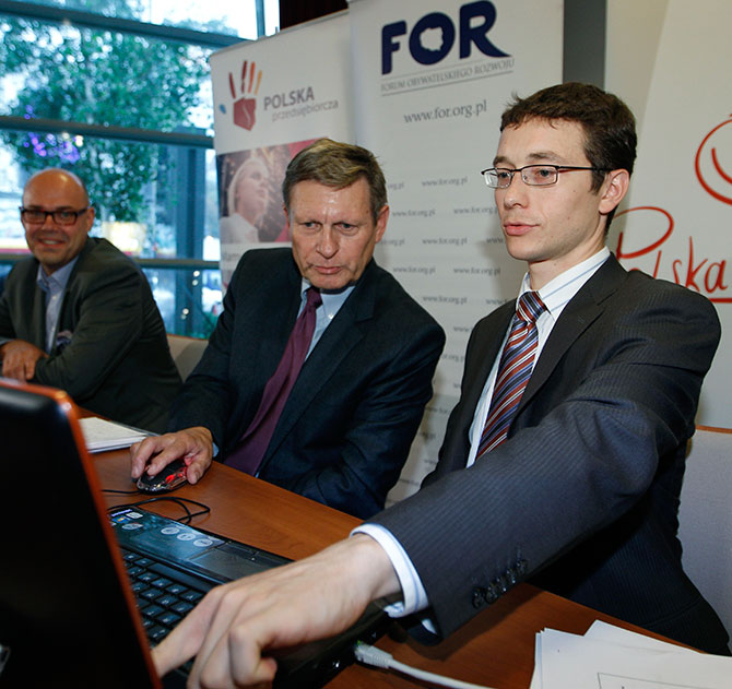 Wiktor Wojciechowski (R) from the Civic Development Forum points on a computer as Poland's former Central Bank Governor Leszek Balcerowicz launches a public debt counter on a public screen in Warsaw.