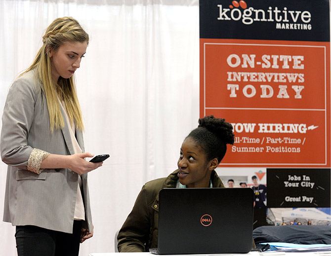 Kognitive Marketing recruiter Maggie O'Rourke (L) conducts a recorded on-site interview with Nafisah Amir (R) at the 2014 Spring National Job Fair and Training Expo in Toronto.