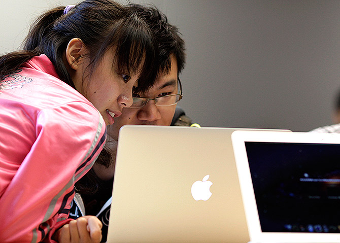 People look at an Apple computer during the inauguration of a new Apple store in Nanjing Road, downtown Shanghai.