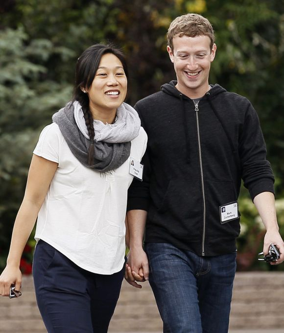 Facebook CEO Mark Zuckerberg walks with his wife Priscilla Chan.