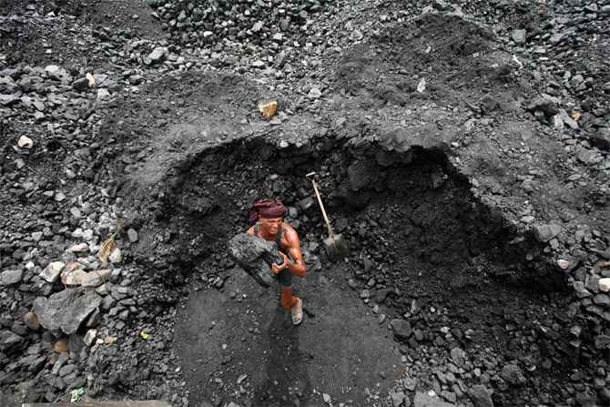 A labourer loads coal onto a truck at a coal yard on the outskirts of Jammu.