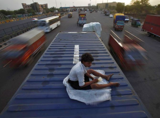The helper of a driver rests on top of his parked truck along a busy highway on the outskirts of New Delhi.