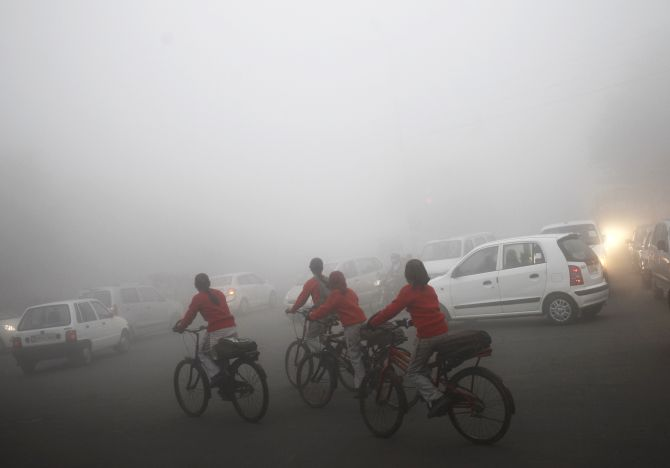 Commuters travel on fog covered roads on a winter morning in New Delhi.