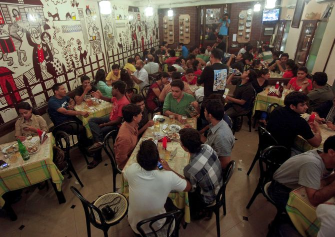 Patrons drink beer and eat food at a pub in Mumbai.
