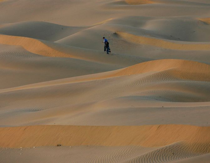 Tourists walk over the Thar Desert at Jaisalmer in the desert Indian state of Rajasthan.