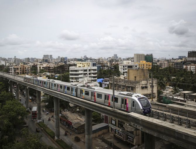 A metro train travels through a residential area in Mumbai.