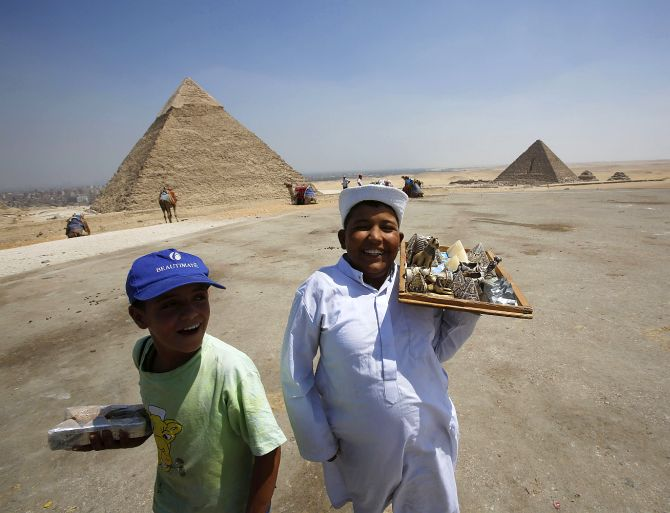 Child vendors react as they attempt to sell souvenirs to tourists at the Giza Pyramids, on the outskirts of Cairo.