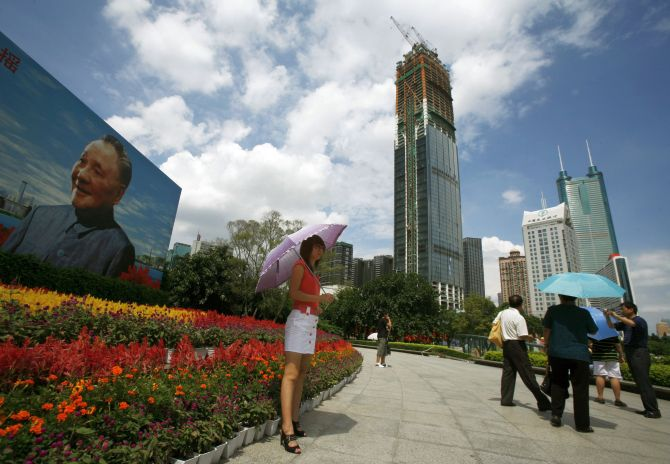 Visitors stand in front of a portrait of the late Chinese leader Deng Xiaoping in the southern Chinese city of Shenzhen.