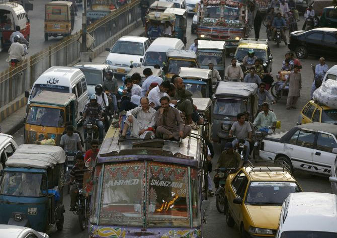 People sit atop a van in the traffic in Karachi.