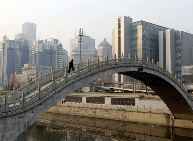 A man walks on a bridge in Beijing.