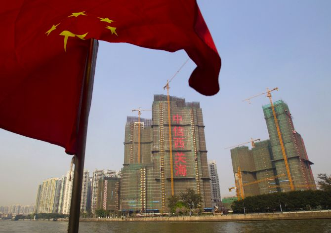 A Chinese national flag flutters on the Pearl River near a construction site in Guangzhou.