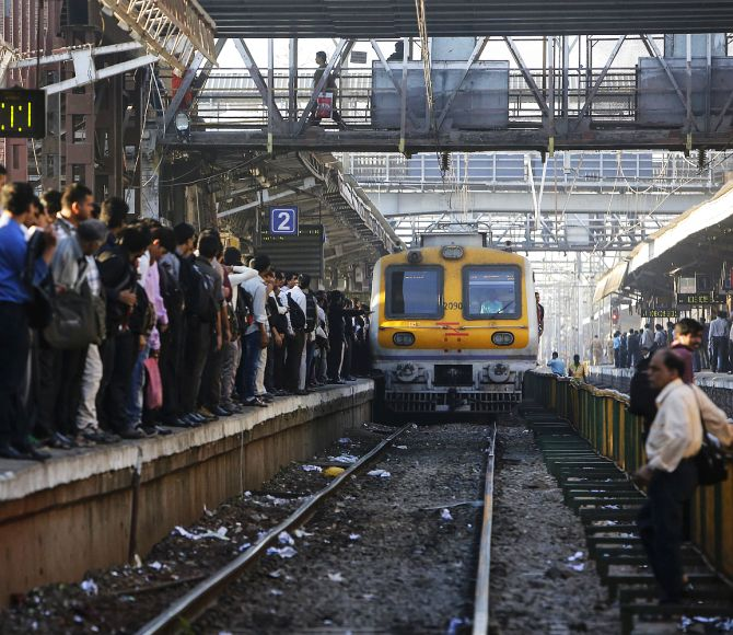 Commuters wait on a crowded railway platform as a train enters a suburban station in Mumbai.