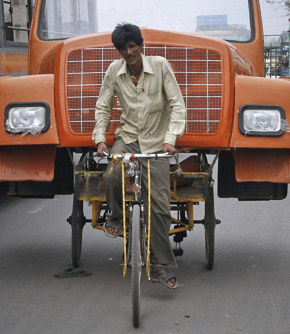 A man uses a cycle rickshaw to transport the front portion of a supply truck.