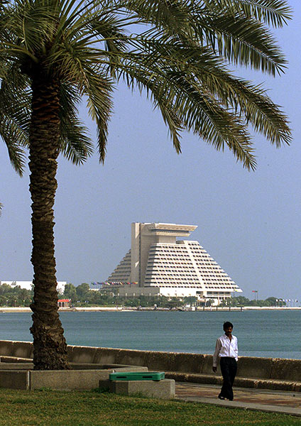 A man walks on the promanade across the bay from a luxurious hotel in Doha.
