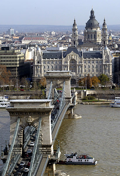 General view of Gresham Palace with Budapest's oldest bridge, Chain Bridge in the foreground and the St. Stephen Basilica in the background.