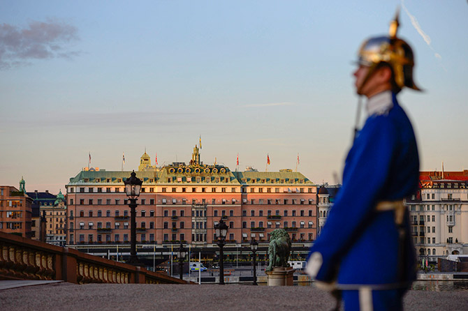 A palace guard stands in front of the Royal Palace while the sun sets over the Grand Hotel in downtown Stockholm.