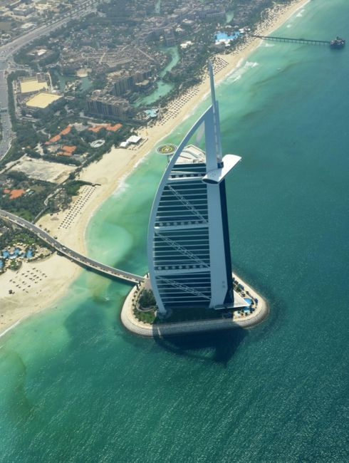 An aerial image with the Burj Al Arab in the foreground, shows the approaching red tide, on the shores of Dubai.