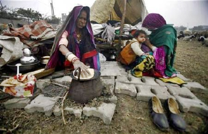 Women cook food outside a makeshift tent on a cold morning at Parthla village in Uttar Pradesh.