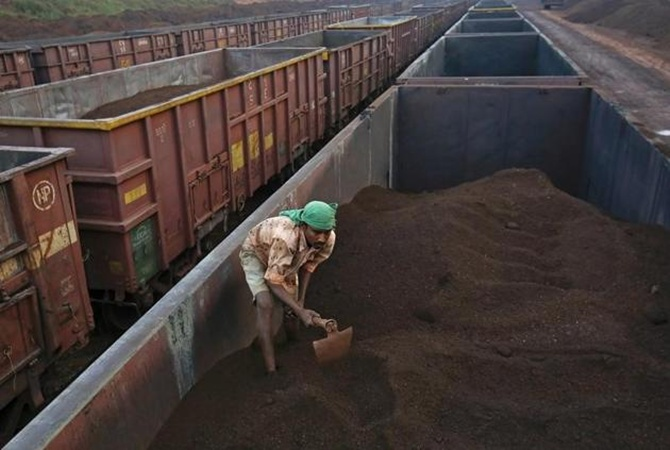 A worker levels the iron ore in a freight train at a railway station at Chitradurga in Karnataka.