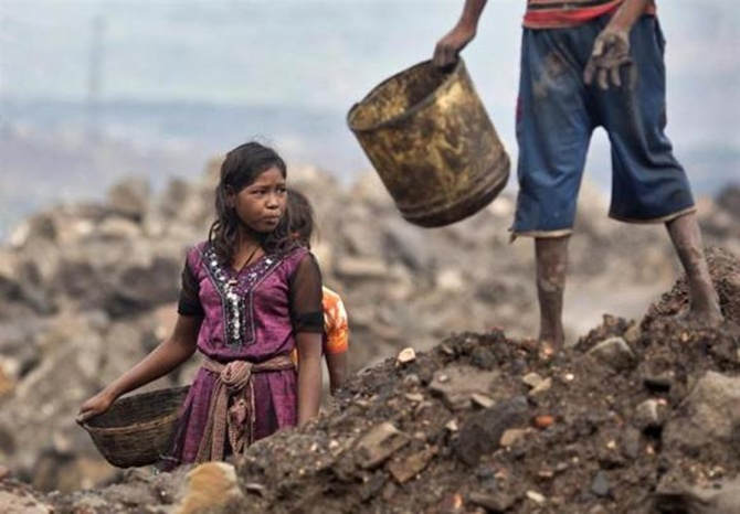 Locals prepare to collect coal from an open cast coal field at Dhanbad district in Jharkhand.