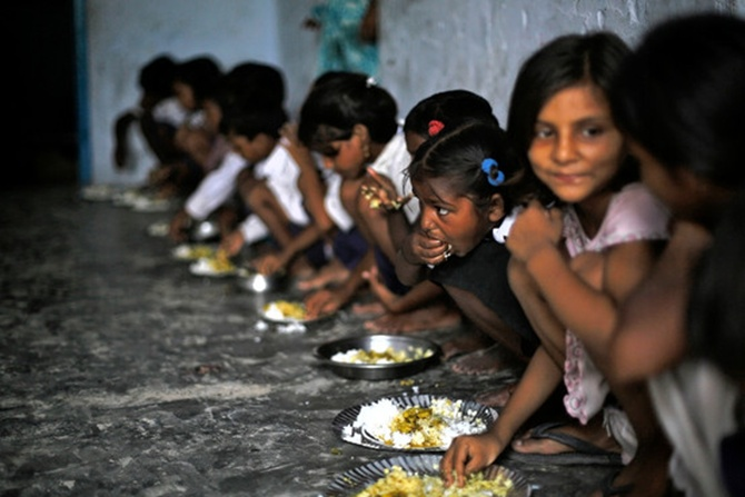 Schoolchildren eat their free midday meal, distributed by a government-run primary school, at Brahimpur village in Bihar.
