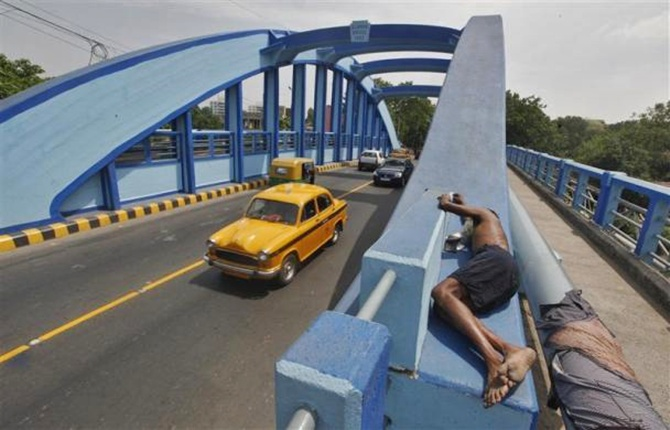 A homeless man sleeps on the sidewalk of a newly painted bridge in Kolkata.