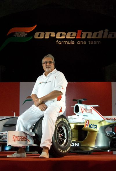 Chairman of Force India F1 team, Vijay Mallya, poses with the Force India Formula One Team car.